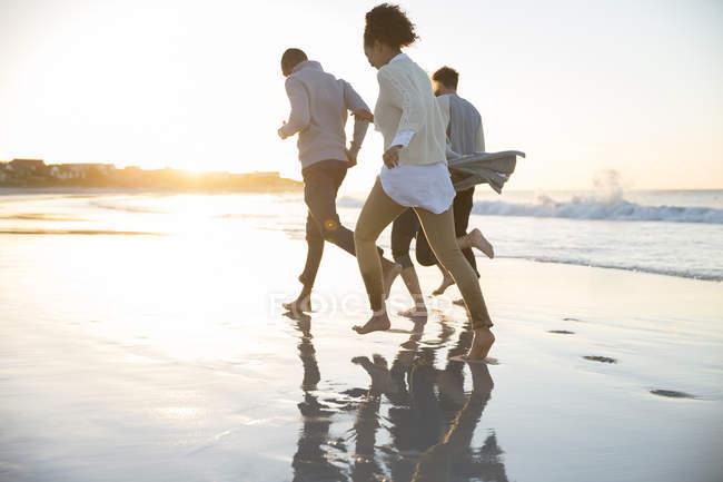 Four friends running ob beach in evening sun — Stock Photo