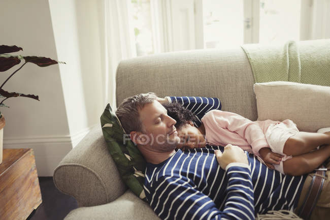 Affectionate, serene multi-ethnic father and daughter napping on sofa — Stock Photo