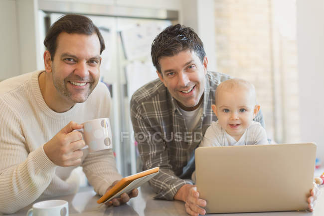 Portrait smiling male gay parents with baby son using digital tablet and laptop in kitchen — Stock Photo