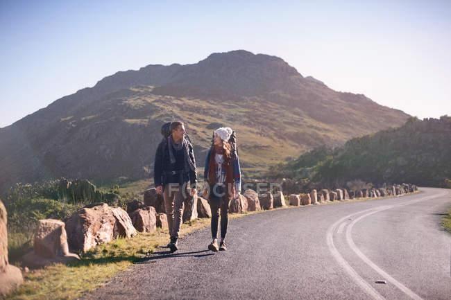 Молоді пара з рюкзаками Піші прогулянки вздовж дороги віддалених, Сонячний — стокове фото
