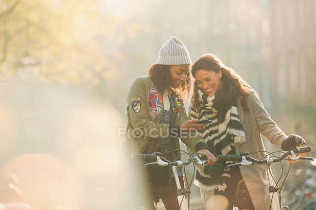 Jeunes femmes amies avec des vélos regardant le téléphone cellulaire sur la rue ensoleillée d'automne — Photo de stock