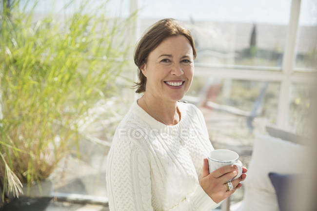 Portrait smiling mature woman drinking coffee in sunny sunroom — Stock Photo