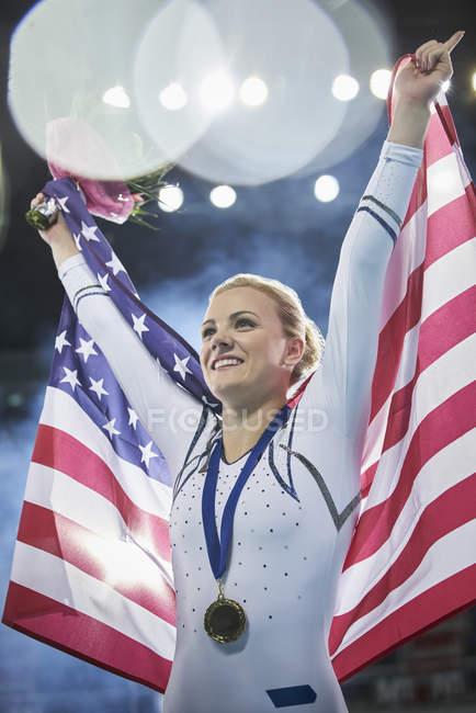 Smiling female gymnast celebrating victory holding American flag — стокове фото