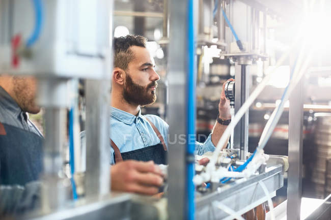 Male brewer adjusting dial on bottling machine in brewery — Stock Photo