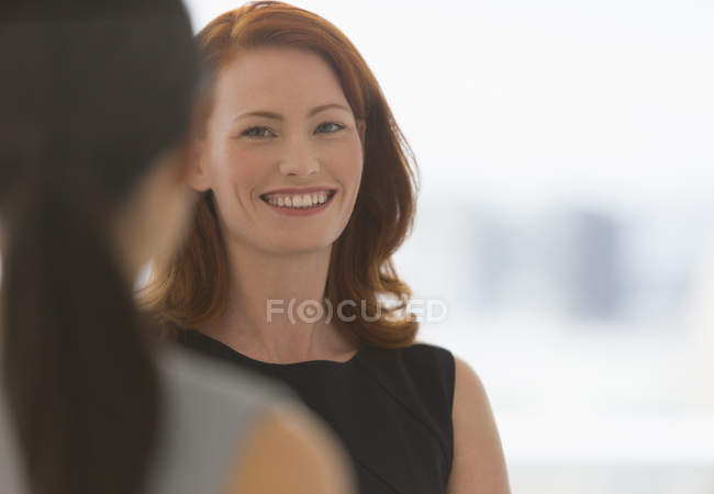 Smiling businesswoman with red hair talking to colleague — Stock Photo