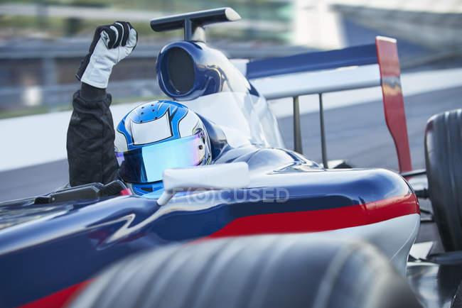 Портрет формула одной гонки автомобилей водитель носить шлем и восхищаться с кулак на спорт трек — стоковое фото