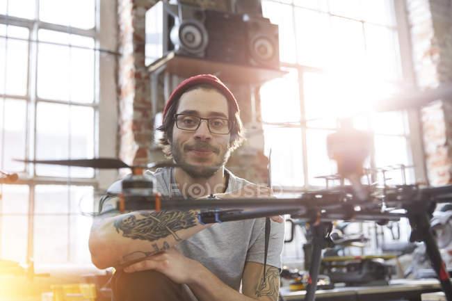 Портрет впевнено чоловічого дизайнер з татуюваннями працює над drone в майстерні — стокове фото