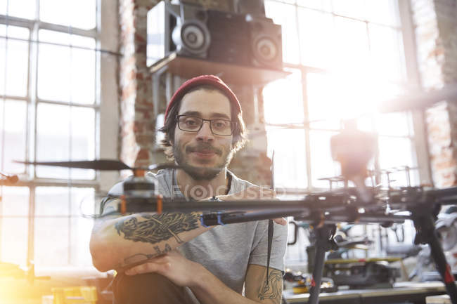 Portrait confident male designer with tattoos working on drone in workshop — Stock Photo