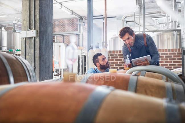 Мужчины виноделы с цифровой планшет проверки деревянные бочки — стоковое фото