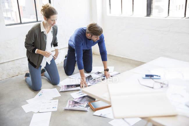 Два молодих людей на колінах на підлозі і, дивлячись на документи — стокове фото