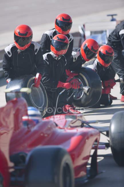 Яма екіпажем з шинами готові наближається до формули один гоночний автомобіль в піт-лейн — стокове фото