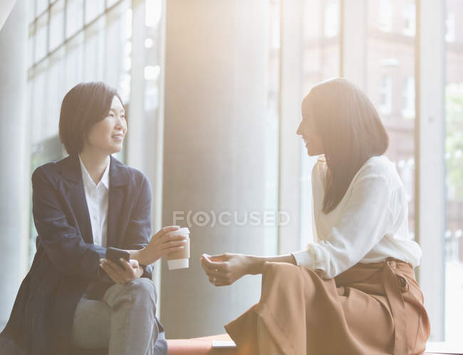 Businesswomen enjoying coffee break talking in sunny lobby — Stock Photo
