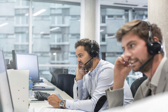 Businessmen with hands-free devices talking on telephone working at computers in office — Stock Photo