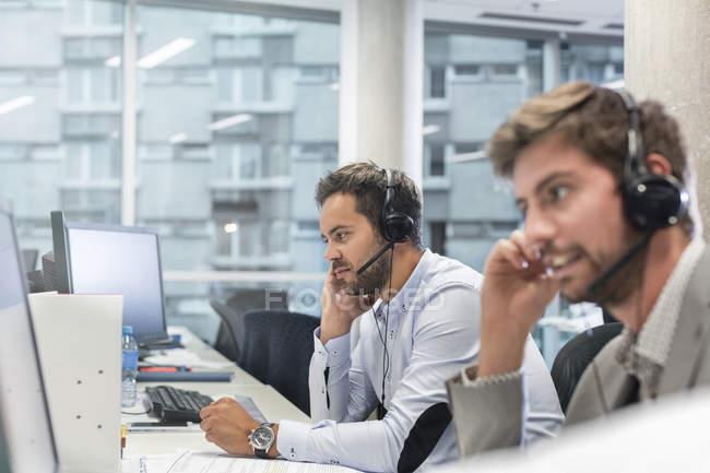 Бизнесмены с громкими устройствами разговаривают по телефону, работая за компьютерами в офисе — стоковое фото