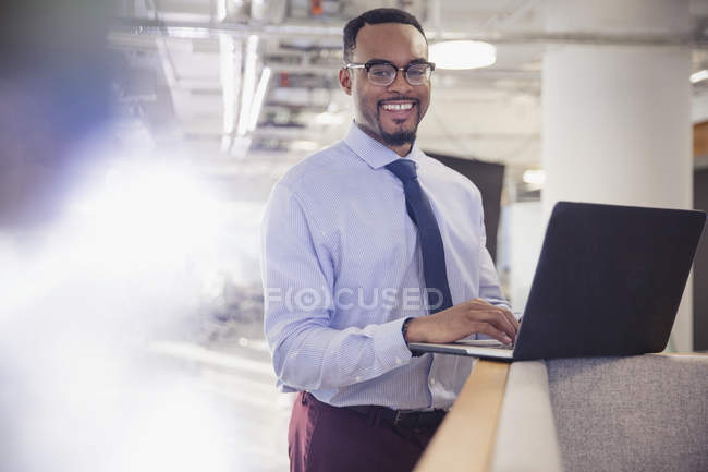 Portrait smiling businessman using laptop in office — Stock Photo