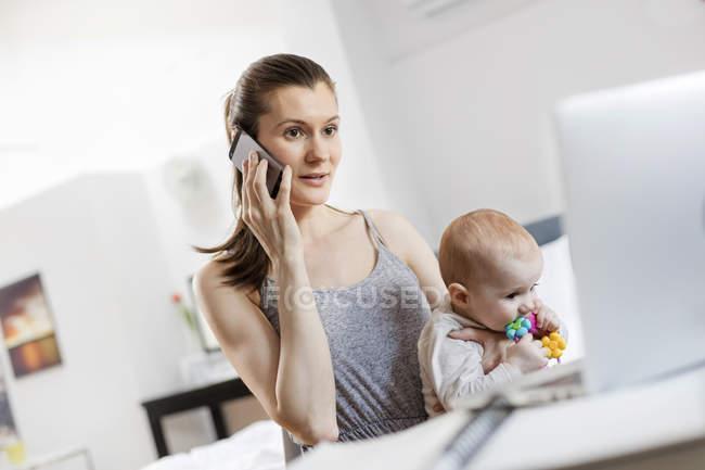 Мать держит малышку дочь, работает за ноутбуком и разговаривает по мобильному телефону — стоковое фото