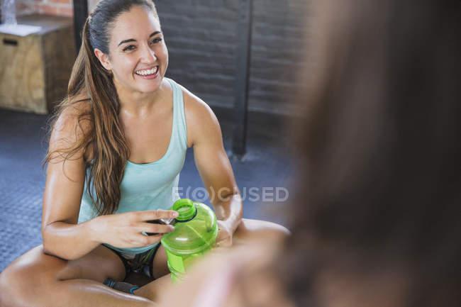 Água potável de jovem a sorrir e a descansar após o treino — Fotografia de Stock