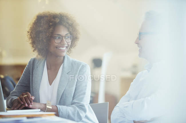 Two office workers talking at desk in modern office — Stock Photo