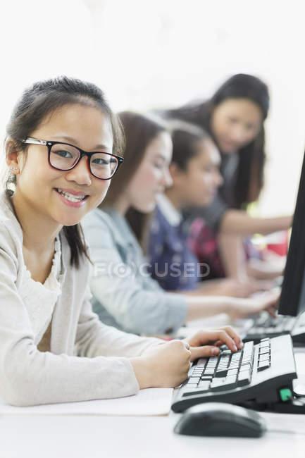 Ritratto sorridente ragazza studente utilizzando il computer in laboratorio informatico — Foto stock