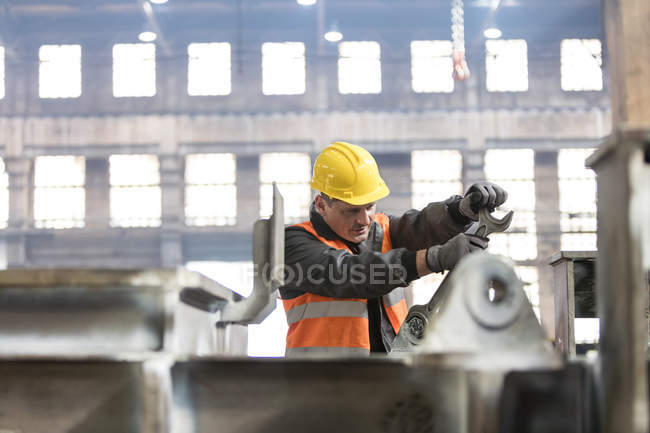 Steel worker using large wrench in factory — Stock Photo