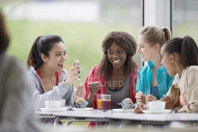 Smiling women drinking coffee and juice using cell phone in cafe post workout — Stockfoto