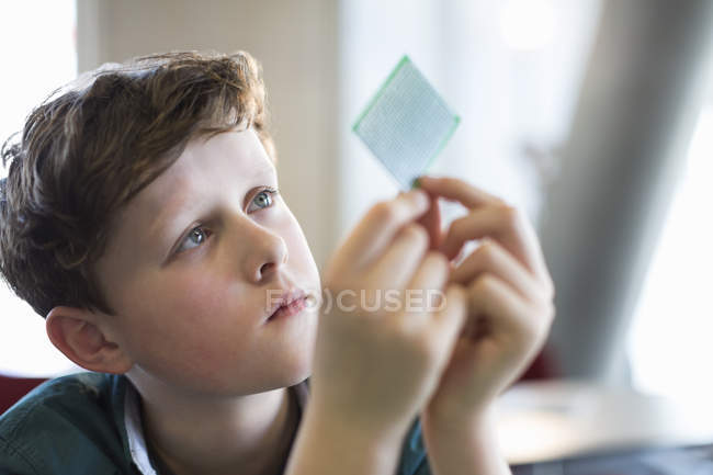 Curious, focused boy examining computer chip in classroom — Stock Photo
