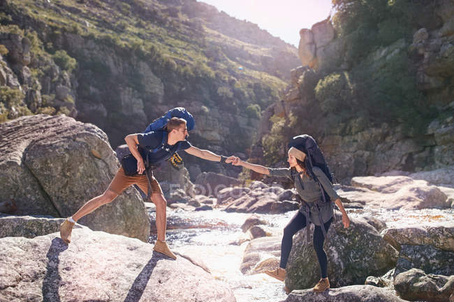 Юнак допомагаючи подруга, Піші прогулянки, перетинаючи Сонячний скелі в потік — стокове фото