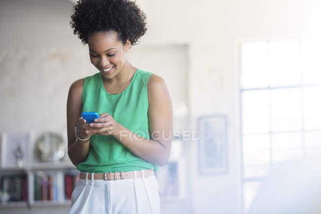 Портрет жінка з чорний Кучеряве волосся, тримаючи мобільного телефону — стокове фото