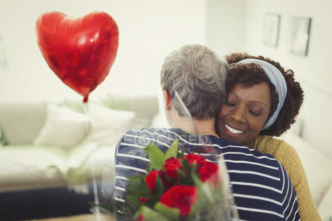 Wife hugging husband giving Valentines Day balloon and rose bouquet — Stock Photo