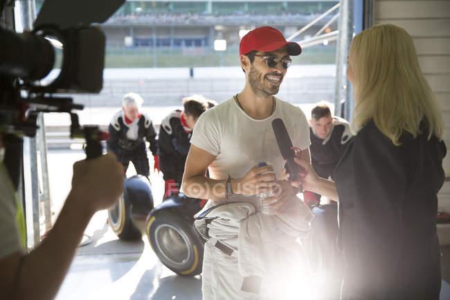 Feminino repórter de notícias entrevistando fórmula masculina um piloto de carro de corrida na garagem de reparação — Fotografia de Stock