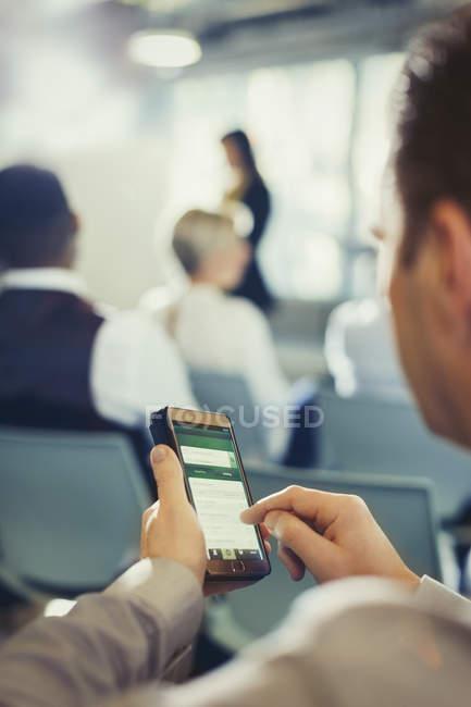 Mensagens de empresário com celular em público de conferência — Fotografia de Stock