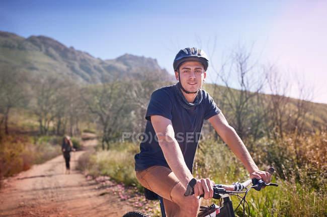 Портрет молодої людини Маунтінбайкінг на віддалених, сонячна стежка — стокове фото