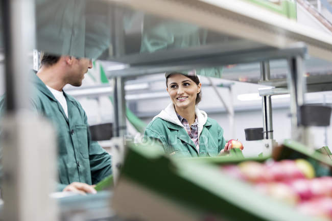 Smiling workers processing apples in food processing plant — Stock Photo