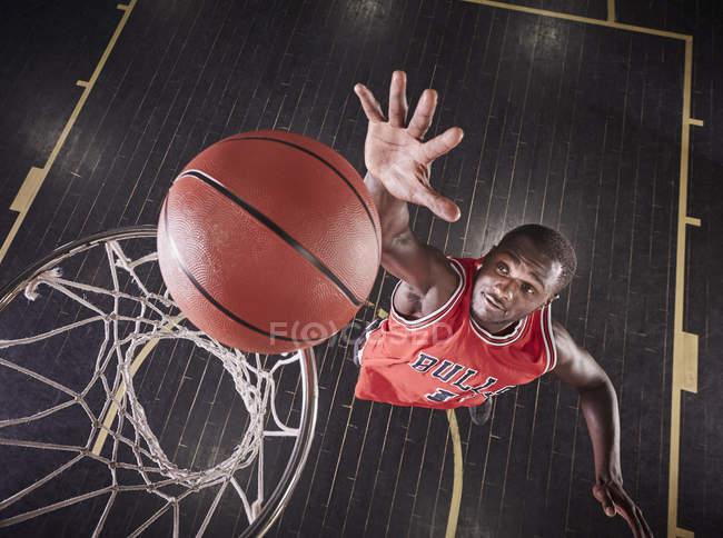 Вид сверху молодых мужчин баскетболист прыжки отскок мяч на ободе баскетбол — стоковое фото