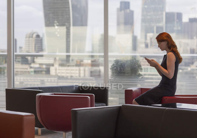 Businesswoman texting with cell phone in urban lounge with city view — Stock Photo