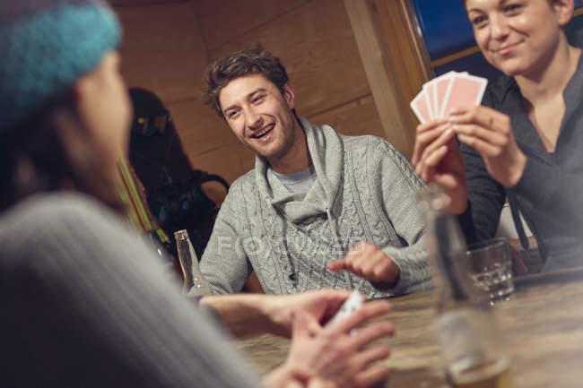 Freunde spielen Karten am Tisch in der Hütte — Stockfoto