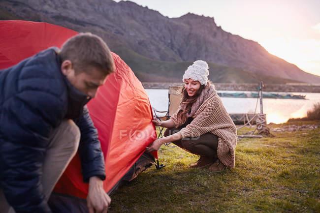 Молода пара пітчинг намет на березі озера кемпінг — стокове фото