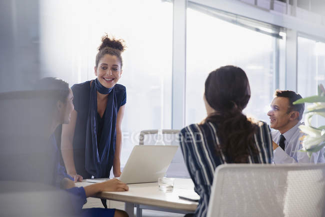 Businesswoman at laptop leading conference room meeting — Stock Photo