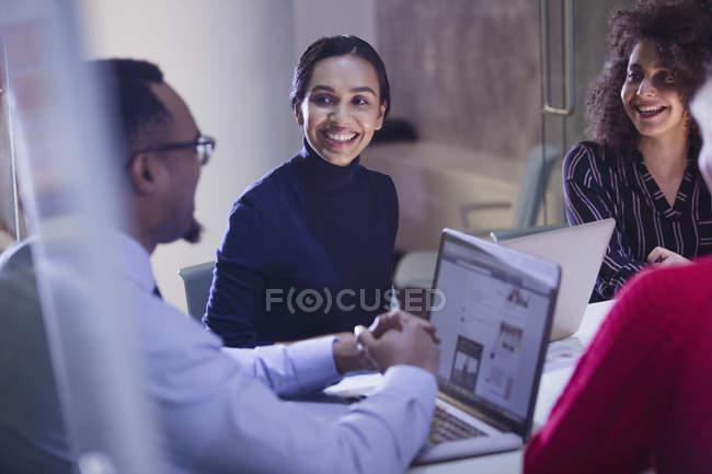 Des hommes d'affaires souriants avec des ordinateurs portables parlant dans la salle de conférence — Photo de stock