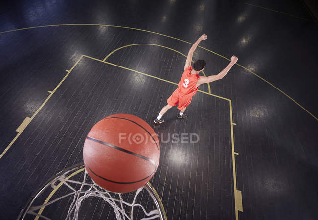 Confident young male basketball player shooting the ball and gesturing, celebrating — Stock Photo