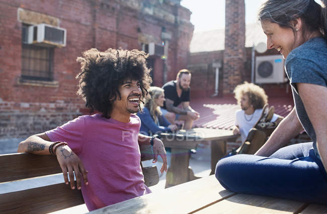 Smiling friends hanging out talking on sunny urban rooftop — Stock Photo