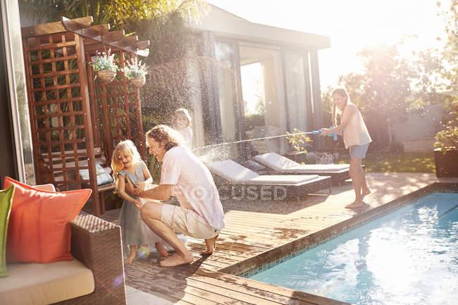 Hija juguetona con pistola de agua rociando padre y hermana con agua al sol junto a la piscina - foto de stock