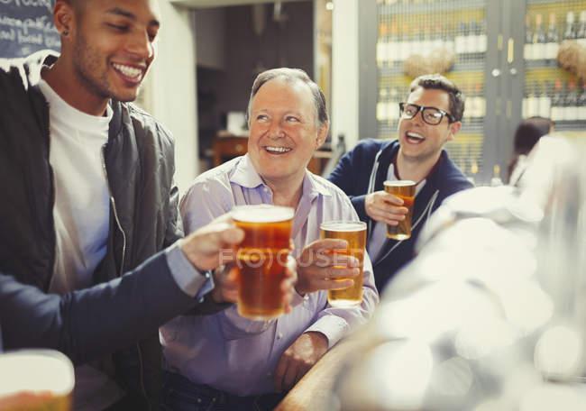 Lächelnde Männerfreunde stoßen an der Bar auf Biergläser an — Stockfoto