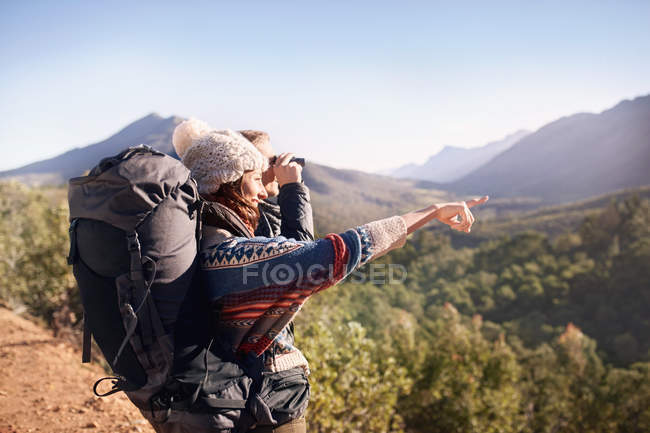 Young couple hiking, looking at sunny view with binoculars — Stock Photo
