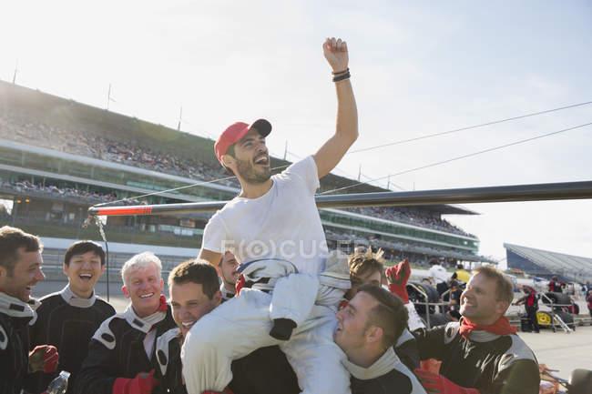 Формули один гоночної команди, несучи cheering драйвер на плечі, святкування перемоги на спорт трек — стокове фото
