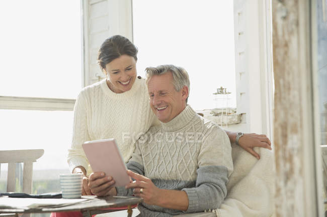 Smiling mature couple using digital tablet at table on sunny sun porch — Stock Photo