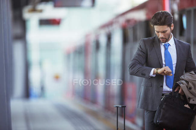Businessman checking his watch in train station — Stock Photo