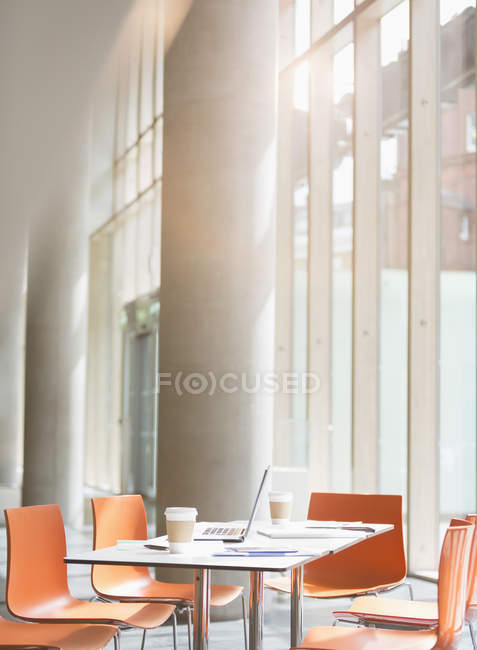 Laptop, coffee and paperwork on table in sunny office — Stock Photo