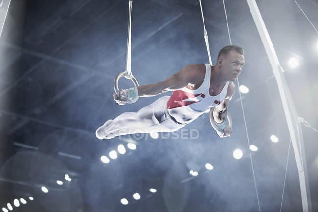 Ginasta masculina se apresentando em anéis de ginástica na arena — Fotografia de Stock