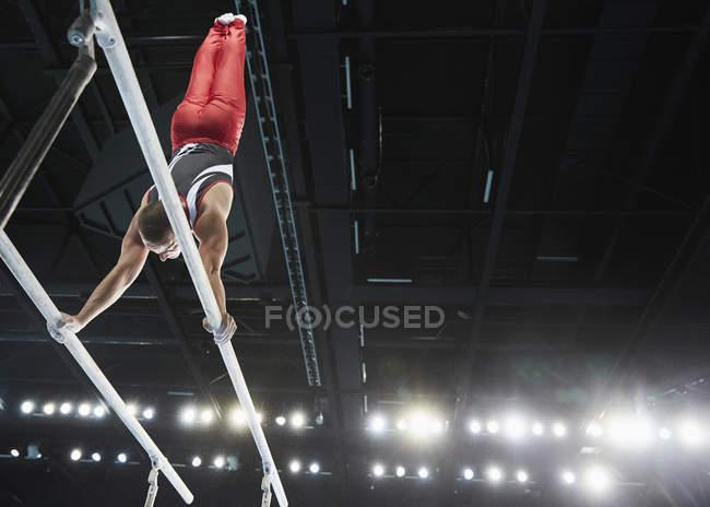 Мужчины гимнаст, выполняя стойку вверх вниз на брусья в Арена — стоковое фото